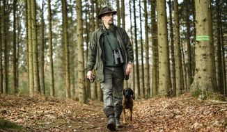 In this Dec. 7, 2018 photo Dirk Gratzel walks with his dog at his hunting ground in Stollberg, western Germany. Gratzel counts his carbon emissions. The software entrepreneur from Germany is among a growing number of people looking for ways to cut their personal greenhouse gas emissions from levels that scientists say are unsustainable if global warming is to be curbed.  (AP Photo/Martin Meissner)