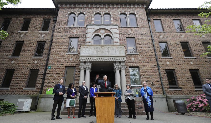 File - In this May 11, 2018 file photo, Washington Gov. Jay Inslee, center, speaks in front of Western State Hospital in Lakewood, Wash. Gov. Inslee unveiled Tuesday, Jan. 11, 2018, his budget and policy plan for fixing the state's struggling mental health system in the coming years. Inslee said he wanted to invest in the troubled Western State Hospital to address safety concerns there, but he didn't mention the rise in assaults at the state's largest psychiatric hospital. (AP Photo/Ted S. Warren, File)
