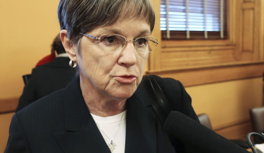 FILE - In this Dec. 4, 2018, file photo, Kansas Gov.-elect Laura Kelly speaks to reporters at the Statehouse in Topeka, Kan. Kelly is selling premium tables at her inaugural ball in January for $10,000. The plan has the inaugural committee and the state ethics commission conferring over compliance with legal limits on contributions to such celebrations. (AP Photo/John Hanna, File)