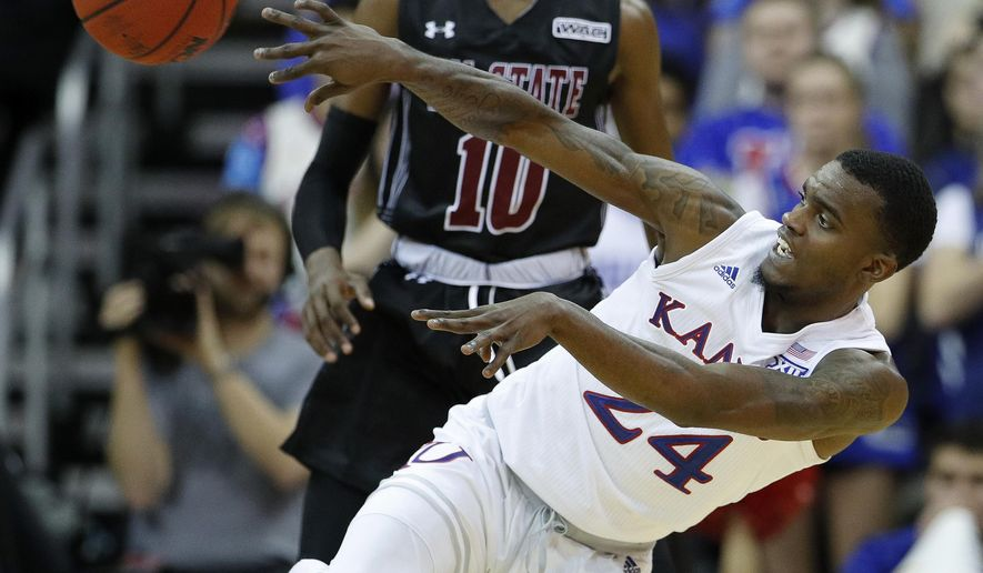 Kansas' Lagerald Vick (24) passes the ball during the second half of the team's NCAA college basketball game against New Mexico State on Saturday, Dec. 8, 2018, in Kansas City, Mo. Kansas won 63-60. (AP Photo/Charlie Riedel)