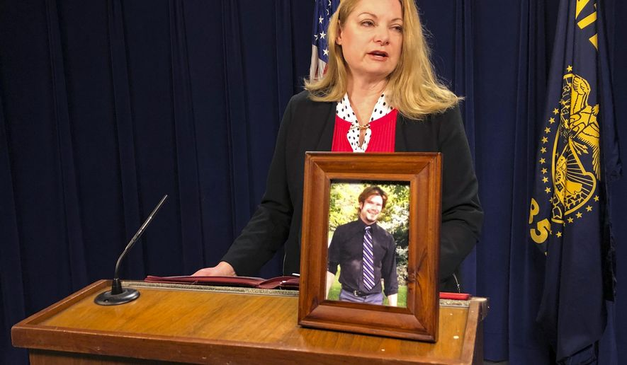 Debra Royal, chief of staff for Oregon Secretary of State Dennis Richardson, describes the overdose death of her nephew, Alex Eliot, seen in the photograph on the lectern, Tuesday, Dec. 11, 2018, in Salem, Ore. A state audit found many holes in a prescription drug monitoring program that's supposed to combat the epidemic. (AP Photo/Andrew Selsky)