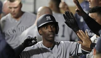 FILE - In this Sept. 7, 2018, file photo, New York Yankees' Andrew McCutchen is greeted in the dugout after he hit a two-run home run during the third inning of a baseball game against the Seattle Mariners, in Seattle. A person familiar with the negotiations tells The Associated Press that All-Star outfielder Andrew McCutchen and the Philadelphia Phillies have agreed to a $50 million three-year contract. The person spoke on condition of anonymity Tuesday, Dec. 11, 2018, because the agreement, which includes a club option for 2022, is subject to a successful physical.(AP Photo/Ted S. Warren, File) **FILE**