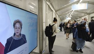 Participants in a U.N. climate conference walk by a screen showing high U.N. official for combatting climate change Patricia Espinoza, as she addresses the delegates in Katowice, Poland, Tuesday, Dec. 11, 2018. (AP Photo/Czarek Sokolowski)