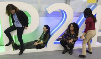Participants in a U.N. climate conference take photos at an installation with the COP24 conference logo, in Katowice,Poland, Tuesday, Dec. 11, 2018.(AP Photo/Czarek Sokolowski)
