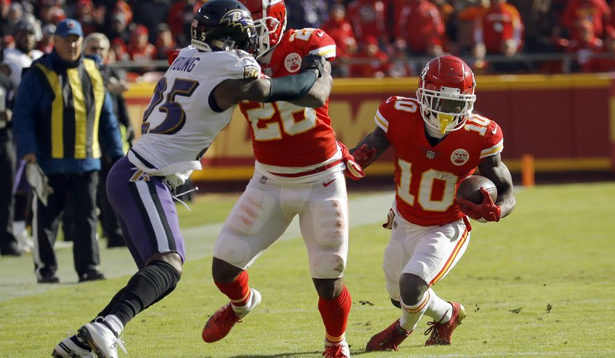 Kansas City Chiefs wide receiver Tyreek Hill (10) carries the ball as running back Damien Williams (26) blocks Baltimore Ravens cornerback Tavon Young (25) during the first half of an NFL football game in Kansas City, Mo., Sunday, Dec. 9, 2018. (AP Photo/Charlie Riedel)
