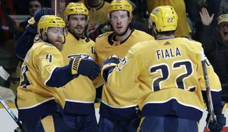 Nashville Predators defenseman Ryan Ellis (4) is congratulated after scoring a goal against the Ottawa Senators in the second period of an NHL hockey game Tuesday, Dec. 11, 2018, in Nashville, Tenn. (AP Photo/Mark Humphrey)