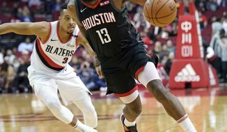 Houston Rockets' James Harden (13) drives past Portland Trail Blazers' CJ McCollum (3) during the first half of an NBA basketball game Tuesday, Dec. 11, 2018, in Houston. (AP Photo/David J. Phillip)