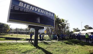A Goodyear billboard emblazoned with the Spanish word for welcome, is posted near a plant entrance company where workers arrived to find the plant is no longer in operation, in Los Guayabos, Venezuela, Monday, Dec. 10, 2018. U.S. tire company Goodyear announced it will no longer continue production in Venezuela as economic conditions in the South American nation continue to deteriorate. (AP Photo/Juan Carlos Hernandez)