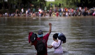 A migrant raises his fist as he nears the Mexican side of the the Suchiate River, that connects Guatemala and Mexico, Monday, Oct. 29, 2018. (AP Photo/Santiago Billy)