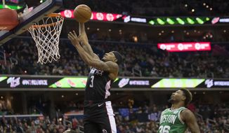 Washington Wizards guard Bradley Beal (3) dunks the ball in front of Boston Celtics guard Marcus Smart (36) during the first half of an NBA basketball game Wednesday, Dec. 12, 2018, in Washington. (AP Photo/Alex Brandon)