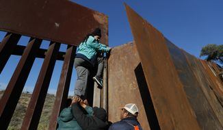 Honduran migrants help a woman cross over the U.S. border wall to San Diego, California, from Playas in Tijuana, Mexico, Wednesday, Dec. 12, 2018. (AP Photo/Moises Castillo) ** FILE **