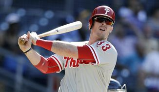 FILE - In this Sunday, Aug. 12, 2018, file photo, the Philadelphia Phillies' Justin Bour watches his single hit during the ninth inning of a baseball game against the San Diego Padres, in San Diego. A person with direct knowledge of the negotiations said Wednesday, Dec. 12, 2018, free agent first baseman and left-handed hitter Justin Bour has reached agreement with the Los Angeles Angels. (AP Photo/Gregory Bull, File)