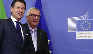 European Commission President Jean-Claude Juncker, right, greets Italian Prime Minister Giuseppe Conte prior to a meeting at EU headquarters in Brussels, Wednesday, Dec. 12, 2018. (Francisco Seco)