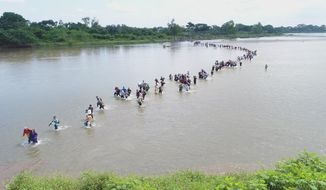 FILE - In this Nov. 2, 2018 file photo, Salvadoran migrants cross the Suchiate River near Tecun Uman, Guatemala, the border with Mexico, as the caravan of Central American migrants make its way north with the stated purpose of entering the United States. Mexico will end the practice of undocumented or illegal crossings over the Suchiate River, which marks much of the border between the two countries, Mexico's Interior Secretary Olga Sanchez Cordero said on Wednesday, Dec. 12, 2018. (AP Photo/Oscar Rivera, File)