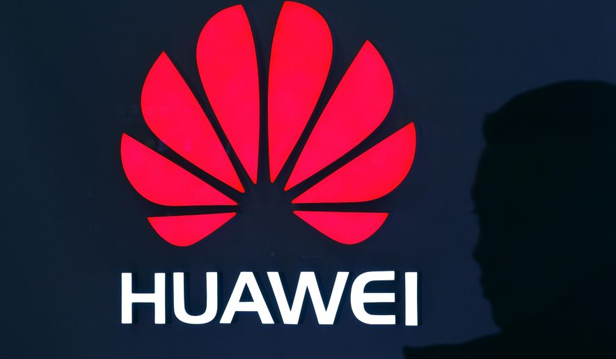 A man is silhouetted as he walks by a Huawei retail store at a shopping mall in Beijing, Tuesday, Dec. 11, 2018. China's foreign minister vowed Tuesday to protect its citizens abroad as a Canadian court decided whether to release a technology executive on bail in a case that has riled U.S.-Chinese relations. (AP Photo/Andy Wong)