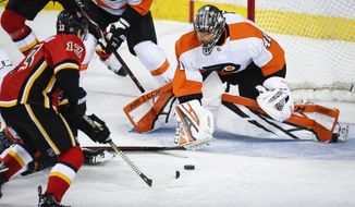 Philadelphia Flyers goalie Anthony Stolarz, right, blocks the net on Calgary Flames' Johnny Gaudreau during the second period of an NHL hockey game, Wednesday, Dec. 12, 2018, in Calgary, Alberta. (Jeff McIntosh/The Canadian Press via AP)