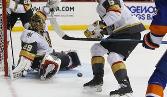 Vegas Golden Knights defenseman Colin Miller (6) watches the puck after a save by goaltender Marc-Andre Fleury (29) against the New York Islanders during the second period of an NHL hockey game, Wednesday, Dec. 12, 2018, in New York. (AP Photo/Noah K. Murray)