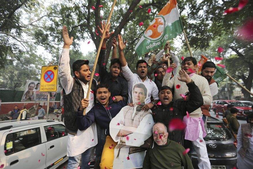Congress party supporters hold a cut-out of party President Rahul Gandhi and celebrate outside the party headquarters in New Delhi, India, Tuesday, Dec. 11, 2018. The Congress party won in the states of Chhatisgarh and Rajasthan, while it was in a close fight with the Bharatiya Janata Party in Madhya Pradesh state. (AP Photo)