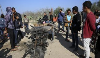In this Monday, Nov. 12, 2018, file photo, Palestinians inspect a vehicle that was destroyed in an Israeli raid that killed seven Hamas Palestinian militants, including a local Hamas commander, late Sunday, east of Khan Younis, southern Gaza Strip. (AP Photo/Adel Hana, File)
