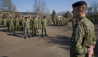 In this photo taken on Thursday, March 22, 2018, members of Kosovo Security Force (KSF) line up for a flag raising ceremony inside the barracks in the southern part of the ethnically divided town of Mitrovica. Kosovo is moving to build itself a regular army, angering neighboring Serbia enough to talk of military intervention _ a seemingly empty threat.  (AP Photo/Visar Kryeziu)