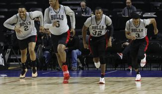 Chicago Bulls Jabari Parker, from left, Cristiano Felicio, Kris Dunn and Shaquille Harrison, warm up at the start of a basketball practice at the Mexico City Arena in Mexico City, Wednesday, Dec. 12, 2018. The Bulls will face Orlando Magic Thursday in the first of two 2018 regular-season NBA games to be played in the high-altitude Mexican capital. (AP Photo/Rebecca Blackwell)