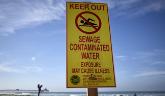 A woman records with a phone along the beach as a sign warns of contaminated water Wednesday, Dec. 12, 2018, at Imperial Beach, Calif. Authorities say more than 6 million gallons (22 million liters) a day of raw sewage has been spilling into Mexico's Tijuana River since Monday night, and the waste is flowing north into Southern California waters. Swimmers and surfers are urged to stay out of the water at some San Diego County beaches. (AP Photo/Gregory Bull)