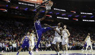 Philadelphia 76ers' Joel Embiid (21) dunks the ball against Brooklyn Nets' Ed Davis (17) during the first half of an NBA basketball game, Wednesday, Dec. 12, 2018, in Philadelphia. (AP Photo/Matt Slocum)