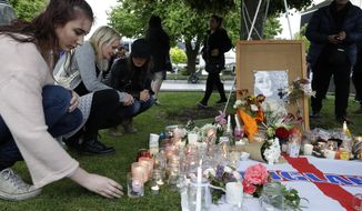 People lay flowers and light candles during a candlelight vigil for murdered British tourist Grace Millane at Cathedral Square in Christchurch, New Zealand, Wednesday, Dec. 12, 2018. (AP Photo/Mark Baker)
