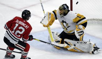 Chicago Blackhawks left wing Alex DeBrincat, left, scores against Pittsburgh Penguins goalie Casey DeSmith during the second period of an NHL hockey game Wednesday, Dec. 12, 2018, in Chicago. (AP Photo/Nam Y. Huh)