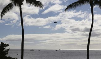 A U.S. Coast Guard helicopter flies over rescue boats at the scene of plane crash off Honolulu, Wednesday, Dec. 12, 2018. Federal Aviation Administration spokesman Ian Gregor said a Hawker Hunter jet went down in the ocean around 2:25 p.m. after taking off from Honolulu's airport. A civilian contractor for the Hawaii Air National Guard who was participating in a military exercise survived after his plane crashed off the coast of Honolulu, authorities said Wednesday.  (AP Photo/Caleb Jones)