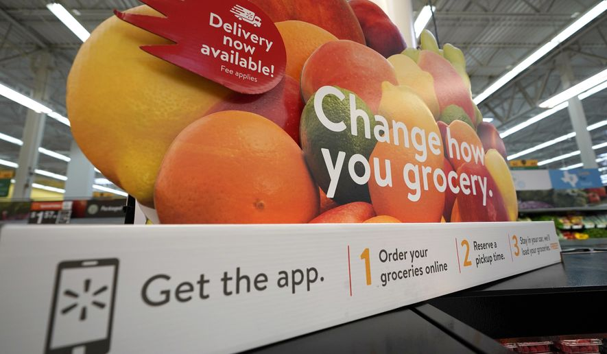 In this Nov. 9, 2018, file photo a sign promotes online and home delivery of groceries at a Walmart Supercenter  in Houston.  (AP Photo/David J. Phillip, File) **FILE**