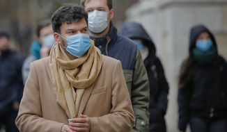 People walk wearing masks during an anti-pollution protest outside the city hall in Bucharest, Romania, Wednesday, Dec. 12, 2018. Dozens of Romanians protested poor air quality in the capital recently ranked one of the most traffic-congested cities in Europe wearing medical face masks to make their point as they walked around the city hall.(AP Photo/Vadim Ghirda)