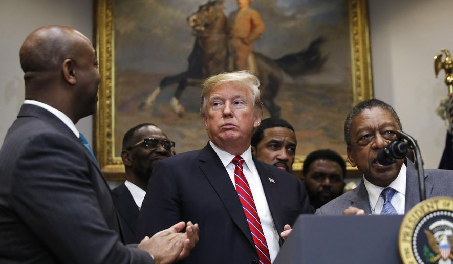 President Donald Trump attends a ceremony for the signing of an executive order establishing the White House Opportunity and Revitalization Council, in the Roosevelt Room of the White House, Wednesday, Dec. 12, 2018, in Washington. At left is Sen. Tim Scott, R-S.C., and speaking at right is Bob Johnson, founder of BET. (AP Photo/Jacquelyn Martin)