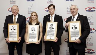 From left, former Michigan coach Red Berenson, three-time Olympic medalist Natalie Darwitz, Nashville Predators general manager David Poile and retired NHL hockey referee Paul Stewart pose with their plaques before being inducted into the U.S. Hockey Hall of Fame, Wednesday, Dec. 12, 2018, in Nashville, Tenn. (AP Photo/Mark Humphrey)