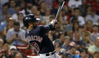 FILE - In this Aug. 22, 2018, file photo, Cleveland Indians' Edwin Encarnacion follows through on his second two-run home run of the night, during the fifth inning of a baseball game against the Boston Red Sox, in Boston. Edwin Encarnacion has been traded to Seattle and first baseman Carlos Santana has returned to the Indians in a three-team deal that also involved Tampa Bay. The Rays got infielder Yandy Diaz and minor league right-hander Cole Slusser from Cleveland. The Indians also acquired first baseman Jake Bauers. The swap came Thursday, Dec. 13, 2018,  at the close of the winter meetings. (AP Photo/Winslow Townson, File)**FILE**