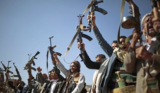 Tribesmen loyal to Houthi rebels hold up their weapons as they attend a gathering to show their support for the ongoing peace talks being held in Sweden, in Sanaa, Yemen, Thursday, Dec. 13, 2018. (AP Photo/Hani Mohammed)