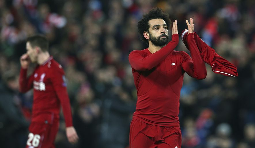 Liverpool forward Mohamed Salah, right, applauds after his team won the Champions League Group C soccer match between Liverpool and Napoli at Anfield stadium in Liverpool, England, Tuesday, Dec. 11, 2018.(AP Photo/Dave Thompson)