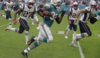 FILE - In this Dec. 9, 2018, file photo, Miami Dolphins running back Kenyan Drake (32) runs for a touchdown during the second half of an NFL football game against the New England Patriots, in Miami Gardens, Fla. The Miami Dolphins are trying to move past the euphoria of their last-play victory over division rival New England and keep their postseason momentum alive at Minnesota. (AP Photo/Lynne Sladky, File)