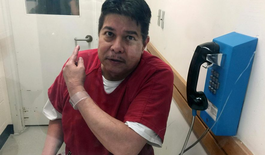 """FILE - In this Nov. 17, 2017, file photo, escaped hospital patient Randall  points to a guard as he sits in an inmate visitor's booth at San Joaquin County Jail before a scheduled court hearing in French Camp, Calif. The attorney representing Saito, who escaped from a Hawaii psychiatric hospital says Thursday, Dec. 13, 2018, his client wants to go to trial. Attorney Michael Green says Randall Saito """"wants to get his story out there."""" In November 2017, Saito walked out of Hawaii State Hospital and was captured days later in Stockton, California.(AP Photo/Terry Chea, File)"""