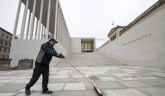 A worker cleans the square in fron of the new James Simon Gallery in Berlin Thursday, Dec. 13, 2018. Berlin has completed a new addition to its Museum Island complex aimed at completing the ensemble of popular museums and making it more user-friendly.  (Bernd von Jutrczenka/dpa via AP)