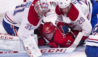 Carolina Hurricanes' Andrei Svechnikov is pushed to the ice by Montreal Canadiens goaltender Carey Price and defenseman Jeff Petry during the second period of an NHL hockey game, Thursday, Dec. 13, 2018 in Montreal. (Paul Chiasson/The Canadian Press via AP)