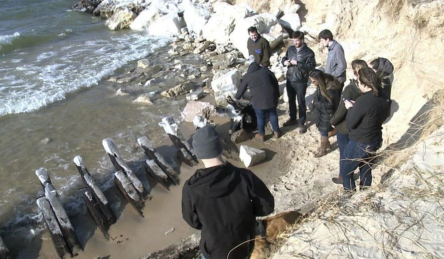 In this Dec. 10, 2018 image made from video and provided by WXMI-TV, people look at the remains of a Lake Michigan shipwreck on shore near Whitehall, Mich. Some experts believe it's the LC Woodruff, a schooner that sank in 1878. (WXMI-TV via AP)