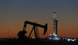 FILE- This Oct. 9, 2018, file photo shows an oil rig and pump jack in Midland, Texas. After a turbulent two months during which oil prices plummeted from a four-year high to a one-year low, investors may wonder what comes next for U.S. crude. (Jacob Ford/Odessa American via AP, File)
