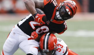 FILE - In this Nov. 25, 2018, file photo, Cincinnati Bengals running back Joe Mixon (28) is tackled by Cleveland Browns middle linebacker Joe Schobert (53) in the first half of an NFL football game in Cincinnati. The Bengals try to maintain their miniscule hopes of a playoff spot when they host the Raiders. (AP Photo/Gary Landers, File)