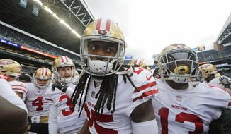 FILE - In this Sunday, Dec. 2, 2018, file photo, San Francisco 49ers cornerback Richard Sherman, center, huddles with teammates before an NFL football game against the Seattle Seahawks, in Seattle. The rematch between the Seahawks and 49ers is on Sunday, Dec. 16. (AP Photo/Elaine Thompson, File)