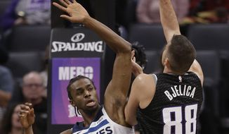Sacramento Kings forward Nemanja Bjelica, right, goes to the basket against Minnesota Timberwolves forward Andrew Wiggins during the first quarter of an NBA basketball game, Wednesday, Dec. 12, 2018, in Sacramento, Calif. (AP Photo/Rich Pedroncelli)