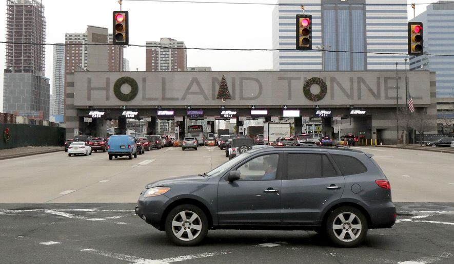 "Holiday decorations adorn the letters on the toll booth structure on the Holland Tunnel approach, Thursday, Dec. 13, 2018, in Jersey City. Motorists are complaining that two circular wreaths and another in the shape of a Christmas tree, symmetrically aligned above the tunnel's lanes, don't look right. An online petition suggests placing the tree over the letter ""A"" instead of the ""N"". (AP Photo/Julio Cortez)"