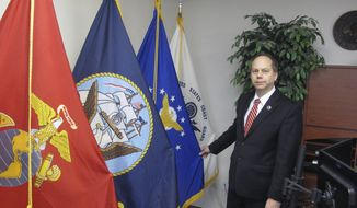 Lonnie Wangen, North Dakota's veterans affairs commissioner, stands next to flags of the armed services at his office in Fargo, N.D., on Wednesday, Dec. 12, 2018. Wangen says legislation supported by Gov. Doug Burgum to exempt military pay and pensions from state income tax might not be a reason for retired vets to stay in North Dakota, but says it sends an important message. Burgum says the initiative is meant to honor veterans and also help fill thousands of open jobs in the state. (AP Photo/Dave Kolpack)