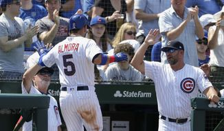 Chicago Cubs' Albert Almora Jr. (5) is greeted at the dugout by manager Joe Maddon, left, and bench coach Brandon Hyde after Almora Jr., score on a single by Anthony Rizzo during the third inning of a baseball game against the Minnesota Twins, Saturday, June 30, 2018, in Chicago. (AP Photo/Charles Rex Arbogast) **FILE**