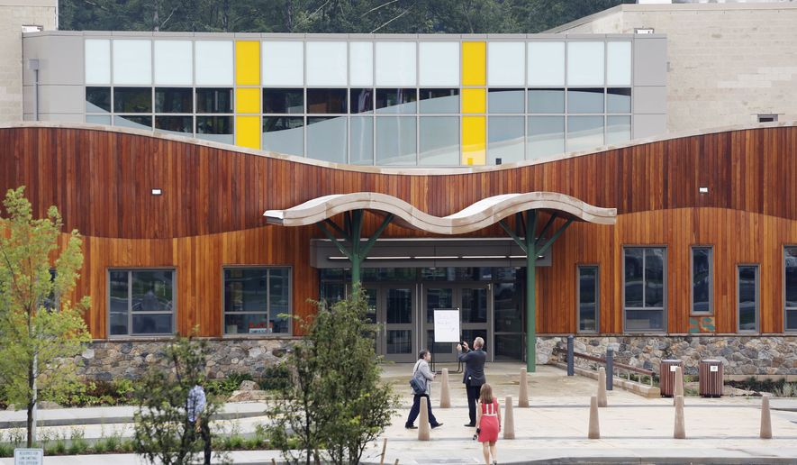 In this July 29, 2016, file photo, people attend an open house at the new Sandy Hook Elementary School in Newtown, Conn., built to replace the one that was demolished where 20 first-graders and six educators were shot and killed in on Dec. 14, 2012. The school was evacuated on Friday, Dec. 14, 2018 -- the sixth anniversary of the mass shooting -- after a bomb threat to the school. (AP Photo/Mark Lennihan, File)